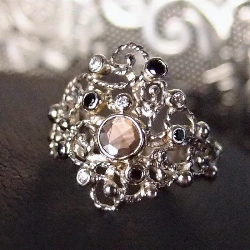 Ażurowy złoty pierścionek ze złotym szafirem i diamentami.