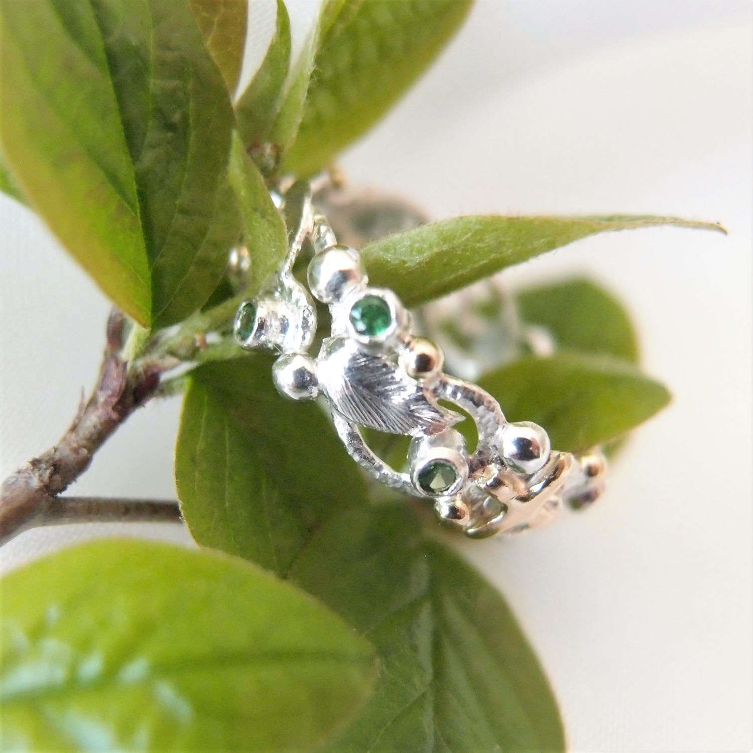 Botanical ring with leaves, green stones and gold