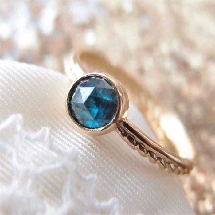 Delikatny złoty pierścionek z niebieskim diamentem