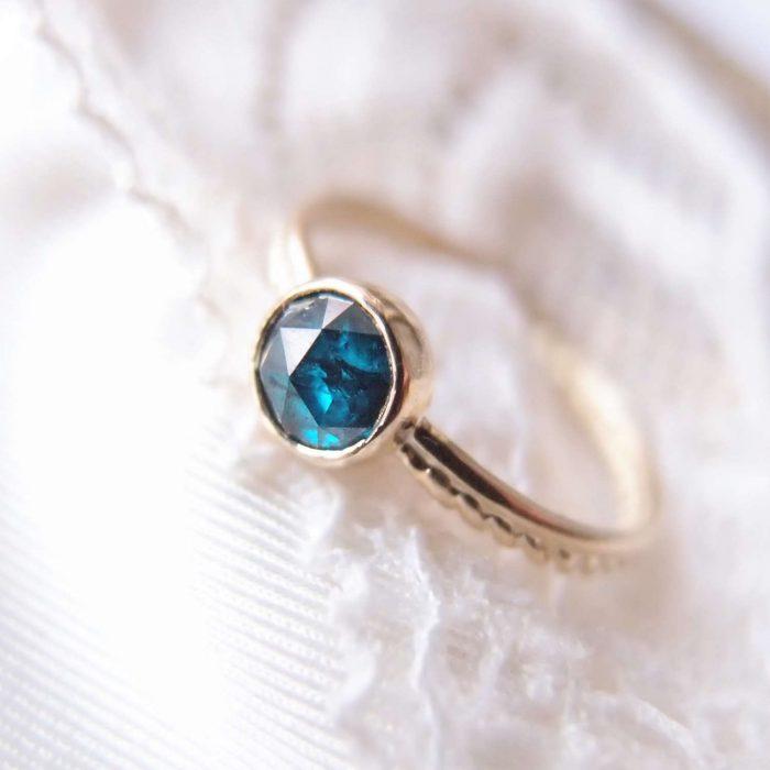 Prosty złoty pierścionek z diamentem w morskim kolorze